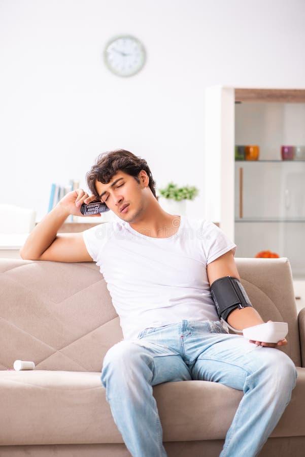 A pressão sanguínea de medição de homem novo em casa imagem de stock