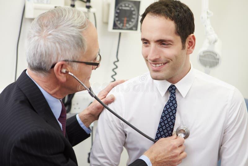 Pressão sanguínea do doutor Taking Male Patient no hospital imagem de stock