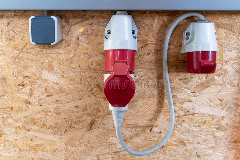 On a pressboard mounted 220 volts and two 380 volt sockets in a factory hall, red and white. On a press board mounted 220 volts and two 380 volt sockets in a stock image