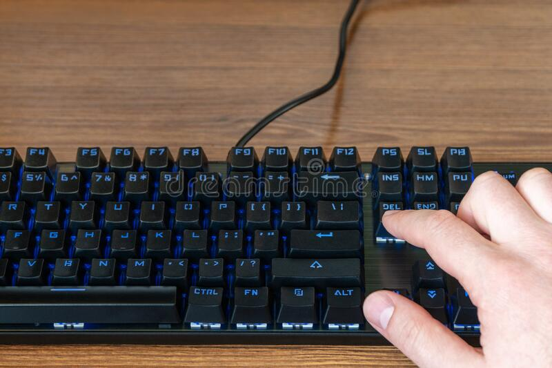 Press the delete key. Index finger of a male hand presses the delete key on a black keyboard with blue backlight royalty free stock image