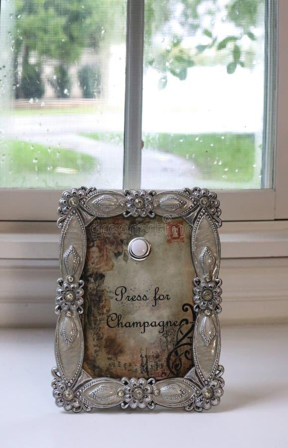 Press för Champagnetecken med knappen att skjuta i utsmyckad silverram sitter framme av trä inramat fönster med skärmen på regnig royaltyfri fotografi