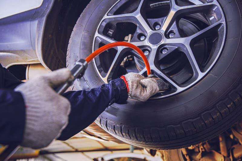 A press?o dos pneus do carro verifica dentro a auto garagem do servi?o imagem de stock