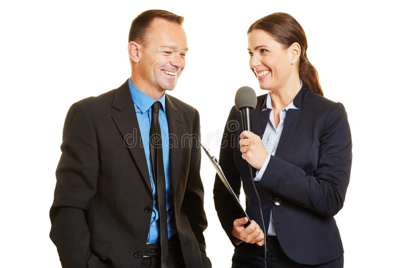 Press officer giving interview to journalist. Press officer of a company giving interview to journalist with a microphone royalty free stock photos