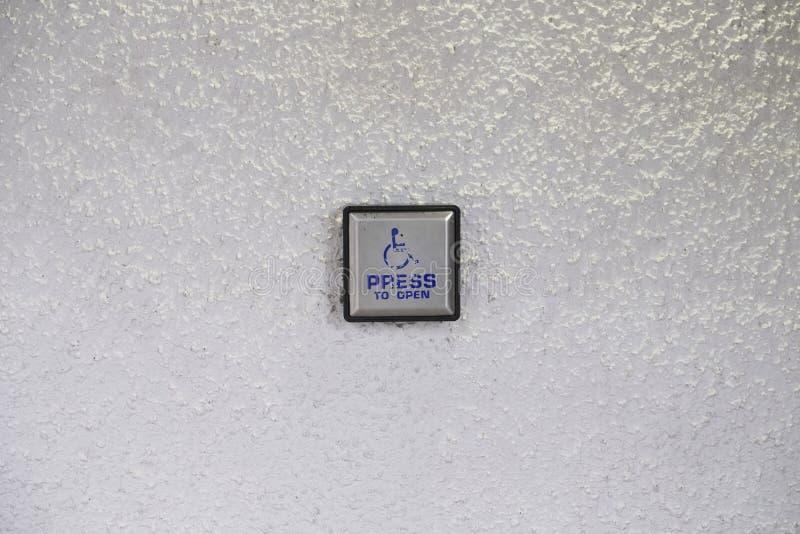 Press som öppnar den automatiska dörren för rörelsehindrade rullstolanvändare, försilvrar metallknappen på den vita väggen arkivbilder