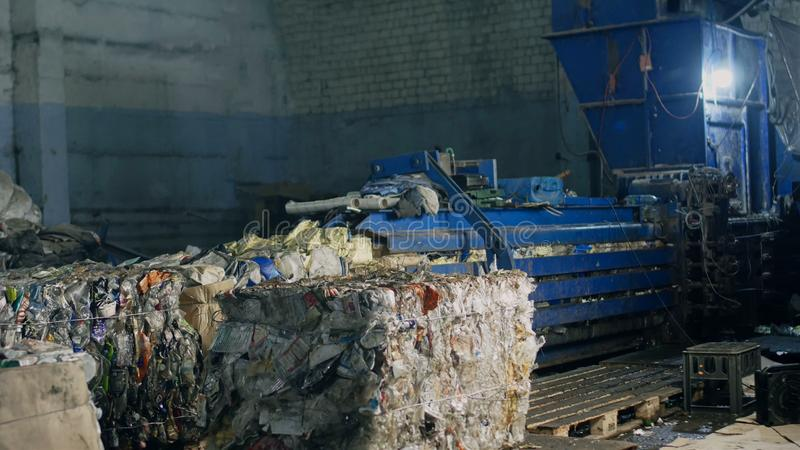 Press at waste recycling plant for pressing plastic and cardboard waste, processing stock photos