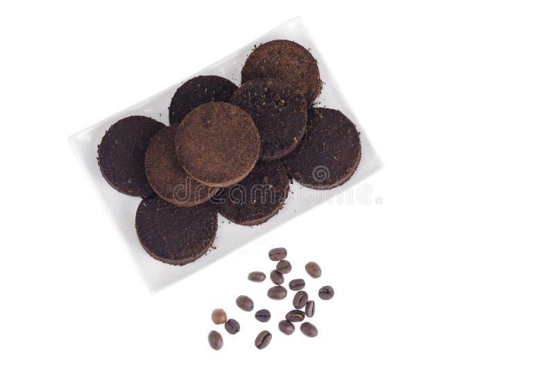 Pressande förlorade kaffebönor på vit bakgrund royaltyfri fotografi
