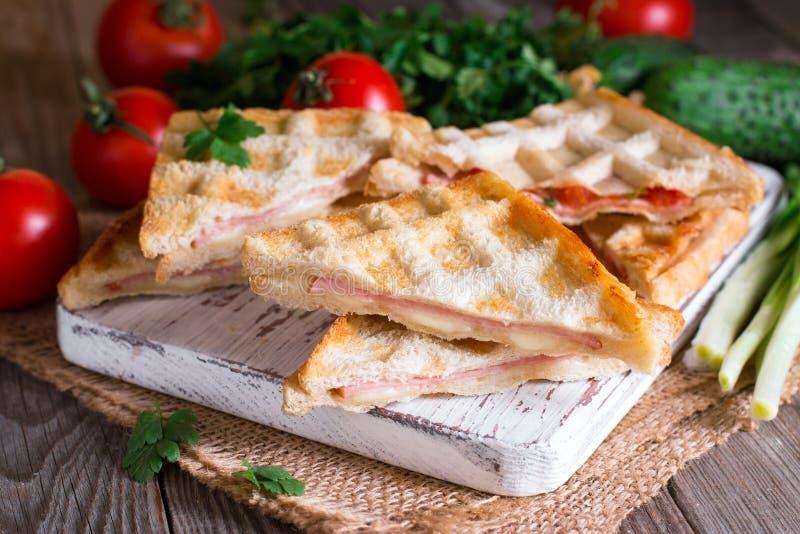 Pressande och rostad dubbel panini med skinka och ost royaltyfri foto