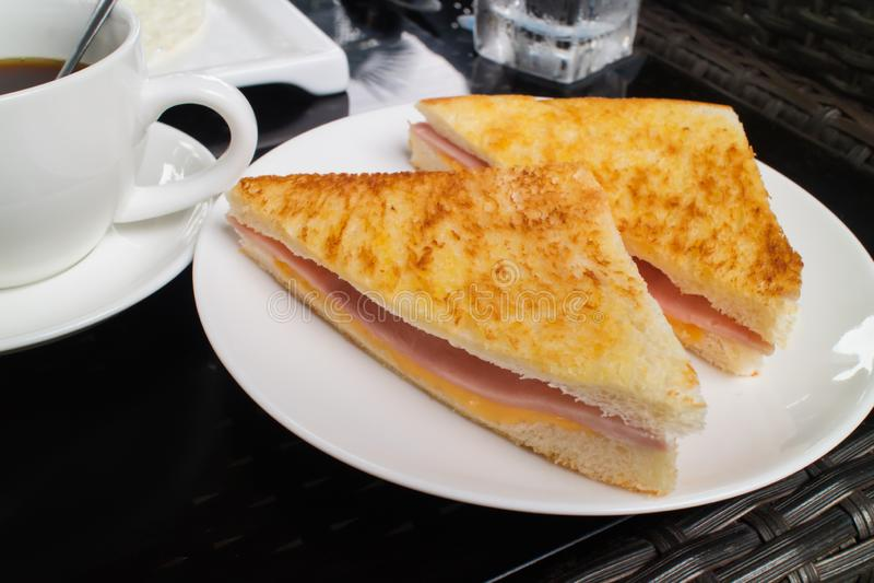 Pressande och rostad dubbel panini med skinka och ost som tjänas som på den vita plattan med en kopp kaffe royaltyfria bilder