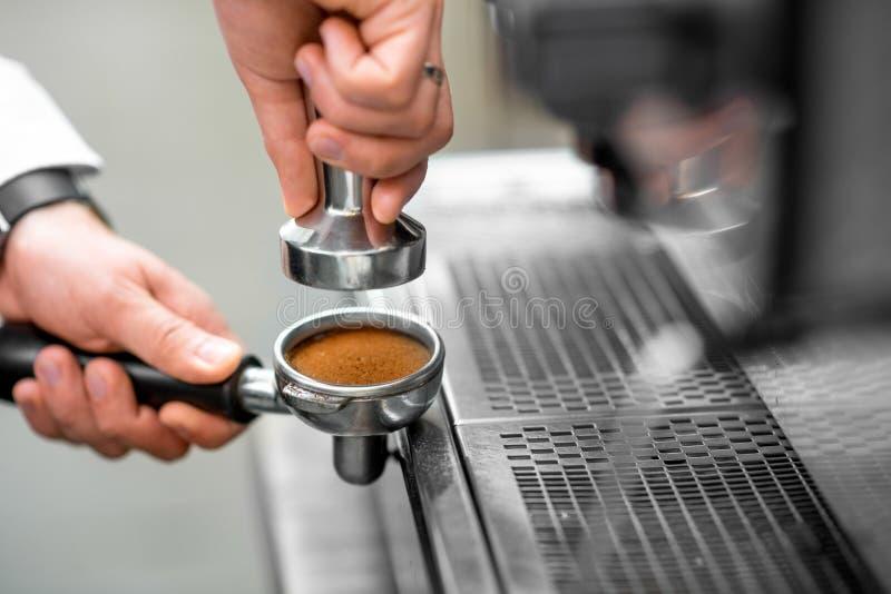 Pressatura del caffè nel supporto a macchina immagini stock