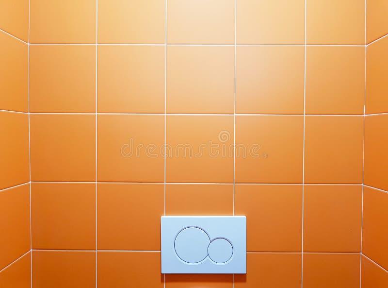 presse à chasse d'eau économique, double plaque de toilette sur mur orange photo stock