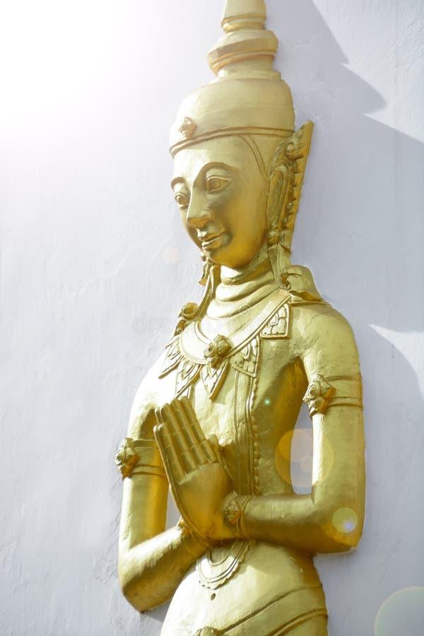 Presse d'or de statue de moine les mains ensemble au coffre ou antérieur images stock