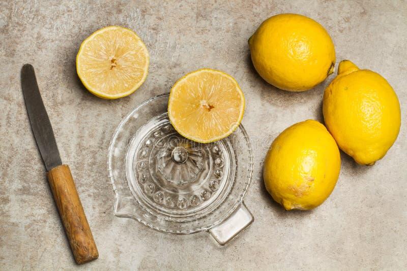 Presse-fruits de citron et en verre photographie stock libre de droits