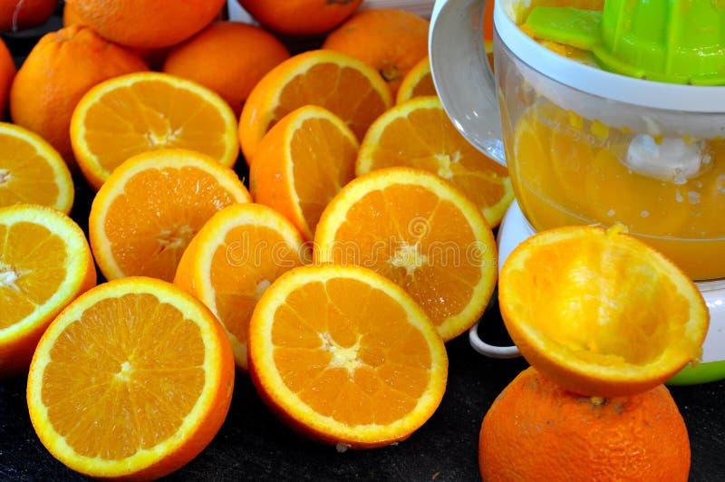 Presse-fruits et beaucoup demi oranges photos stock