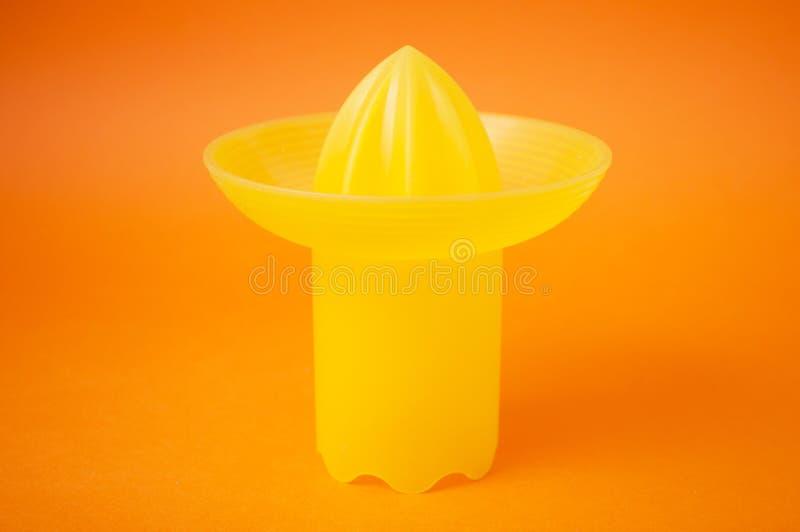 Presse-fruits jaune de fruit sur le fond orange images stock