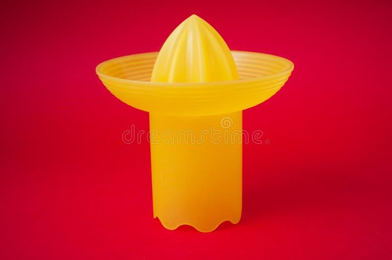 Presse-fruits jaune de fruit sur le fond rouge images stock