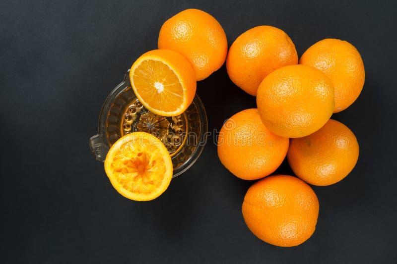 Presse-fruits manuel avec des oranges sur l'obscurité photos stock