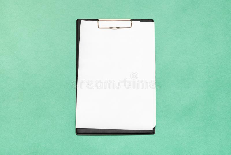 Presse-papiers avec des feuilles de livre blanc de blanc sur le vert photos stock