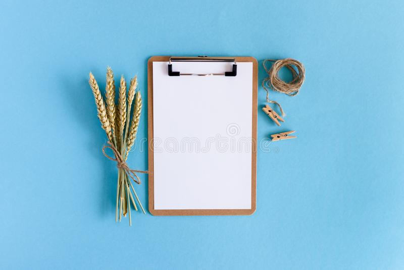 Presse-papiers avec le papier blanc blanc, bouquet des épillets de blé, corde de ficelle, pinces à linge en bois photographie stock