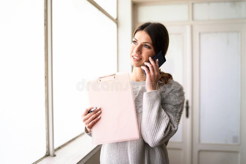 Presse-papiers de participation de jeune femme parlant au téléphone au travail images libres de droits