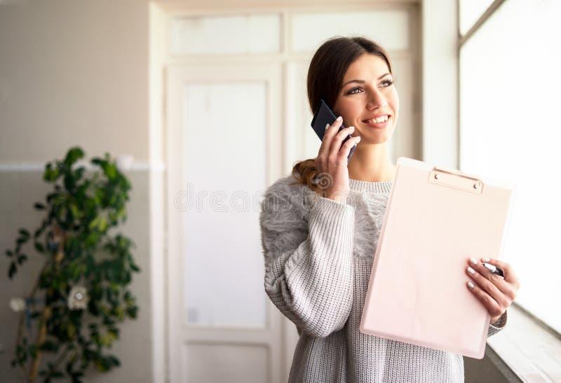 Presse-papiers de participation de jeune femme parlant au téléphone au travail photographie stock