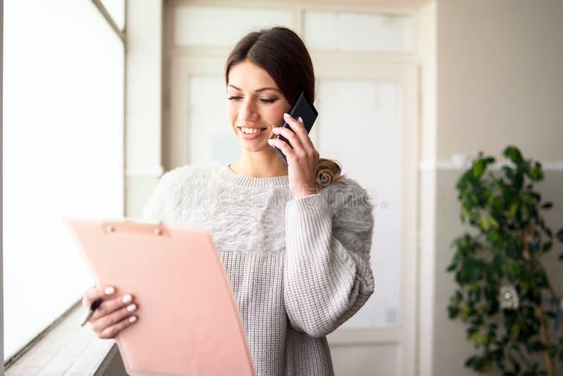 Presse-papiers de participation de jeune femme parlant au téléphone au travail photo libre de droits