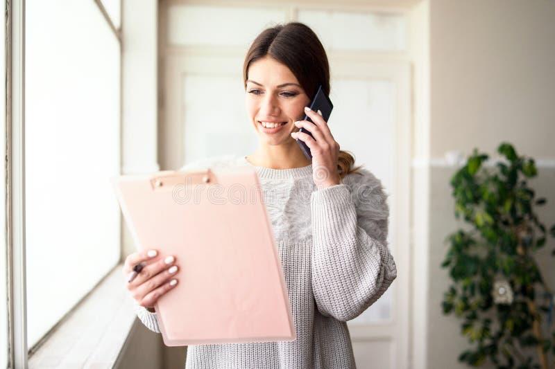 Presse-papiers de participation de jeune femme parlant au téléphone au travail photos stock