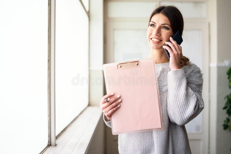 Presse-papiers de participation de jeune femme parlant au téléphone au travail photo stock