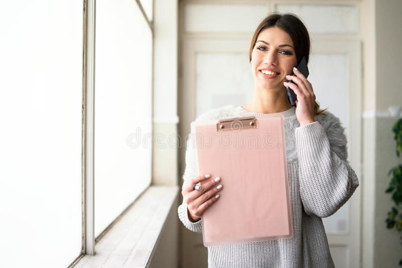 Presse-papiers de participation de jeune femme parlant au téléphone au travail photographie stock libre de droits