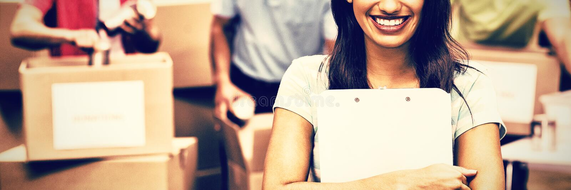 Presse-papiers se tenant volontaire de sourire de femelle photo libre de droits