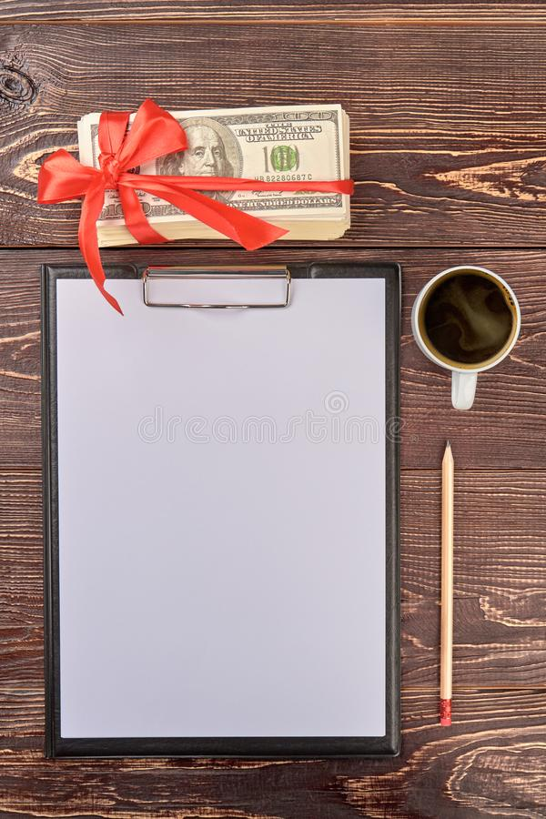 Presse-papiers vide avec le crayon, la tasse de thé et le cadeau d'argent photographie stock libre de droits