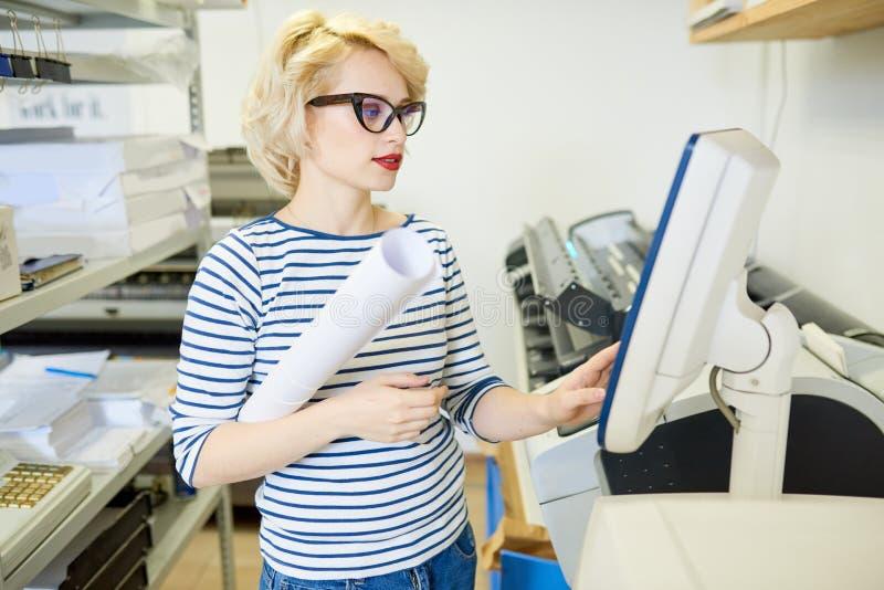 Presse typographique fonctionnante de femme blonde photos libres de droits
