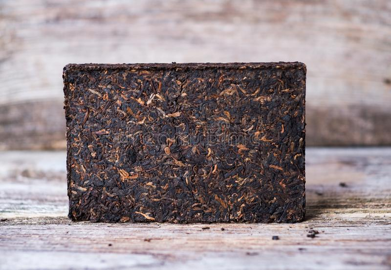 Pressed Chinese Puer tea brick. Pressed Chinese Puer tea ripe brick on a wooden table royalty free stock photos