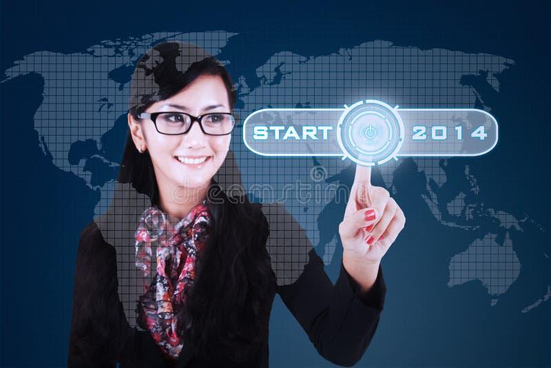 Pressing a button of symbol new future. Happy asian businesswoman pressing a button of symbol new future on virtual screen stock photo