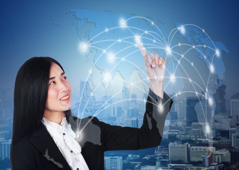 Pressing de femme d'affaires sur l'écran tactile vitual de réseau de carte du monde image stock