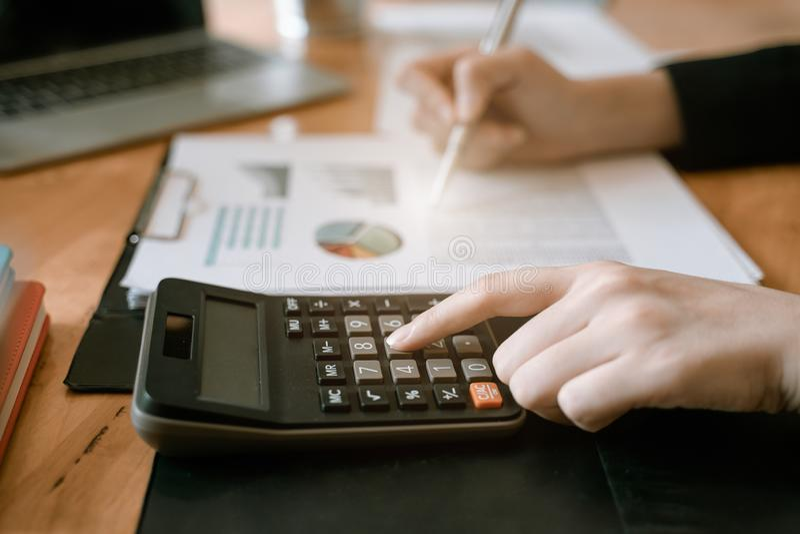 Pressing de main de femme d'affaires sur la calculatrice pour l'estimation de co?t calculatrice photos stock