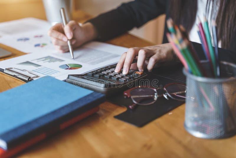 Pressing de main de femme d'affaires sur la calculatrice pour l'estimation de co?t calculatrice photographie stock libre de droits
