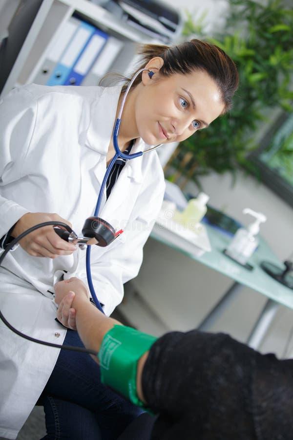 Pression de mesure de patients de docteur féminin photographie stock libre de droits