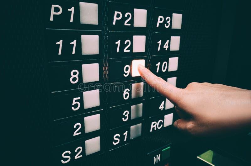 Pressionando o botão do elevador com as mãos, tocando a superfície pública com germes, cuidados pessoais de higiene para a COVID- imagem de stock