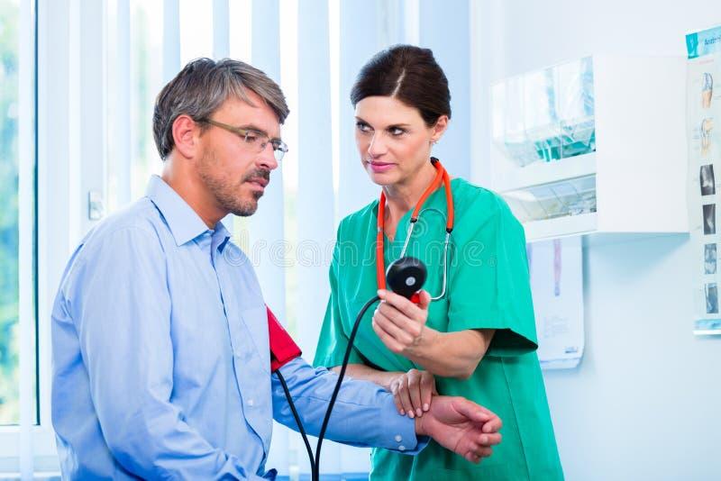 Pressione sanguigna di misurazione del medico fotografie stock