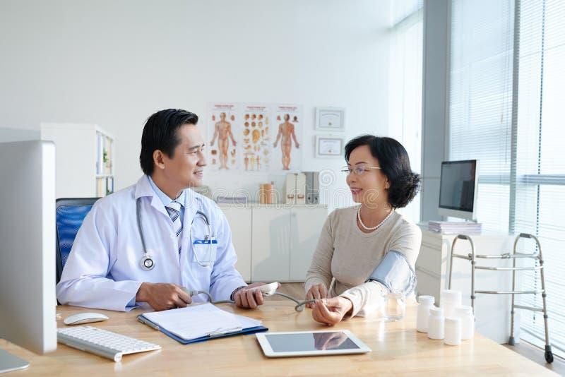 Pressione sanguigna di misurazione del paziente immagini stock