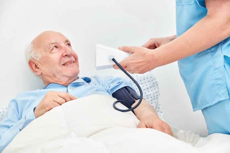 Pressione sanguigna di misurazione dell'infermiere dall'anziano fotografia stock libera da diritti