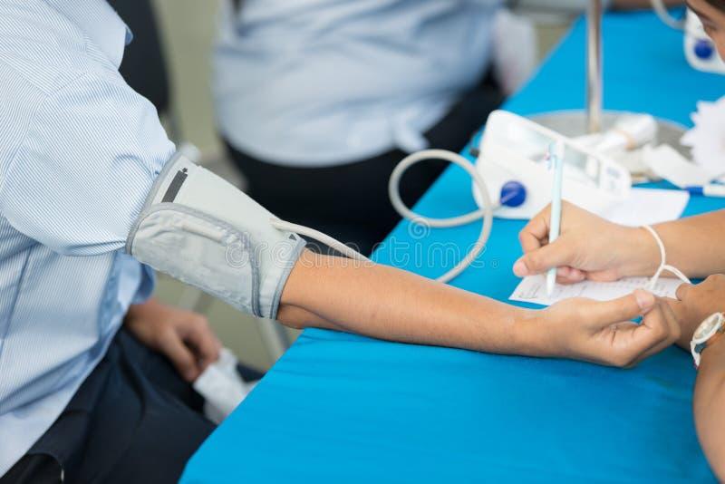Uomo Senior D'esame Di Pressione Sanguigna Dell'infermiere..