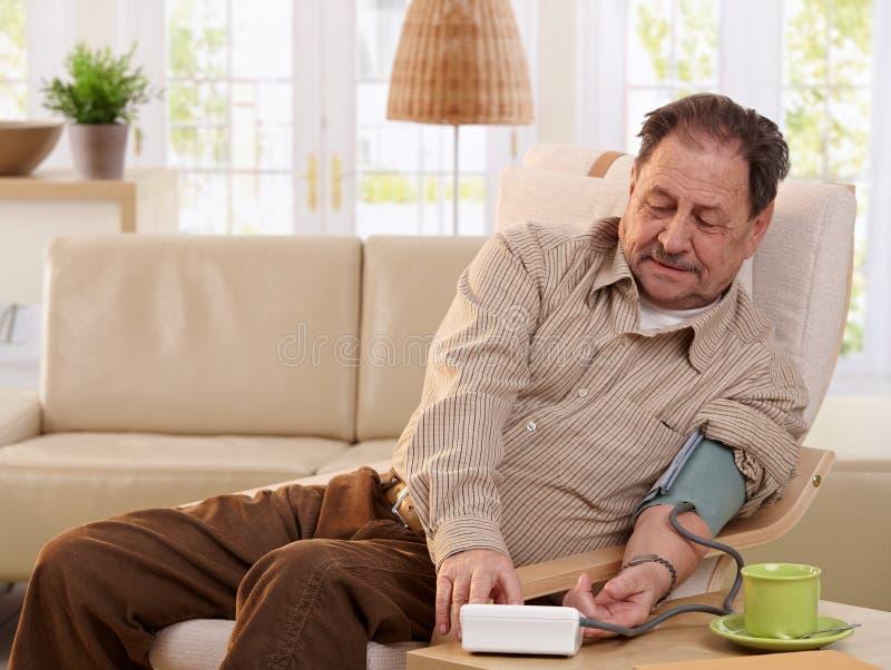 Pressione sanguigna di misurazione dell'uomo anziano a casa fotografie stock libere da diritti