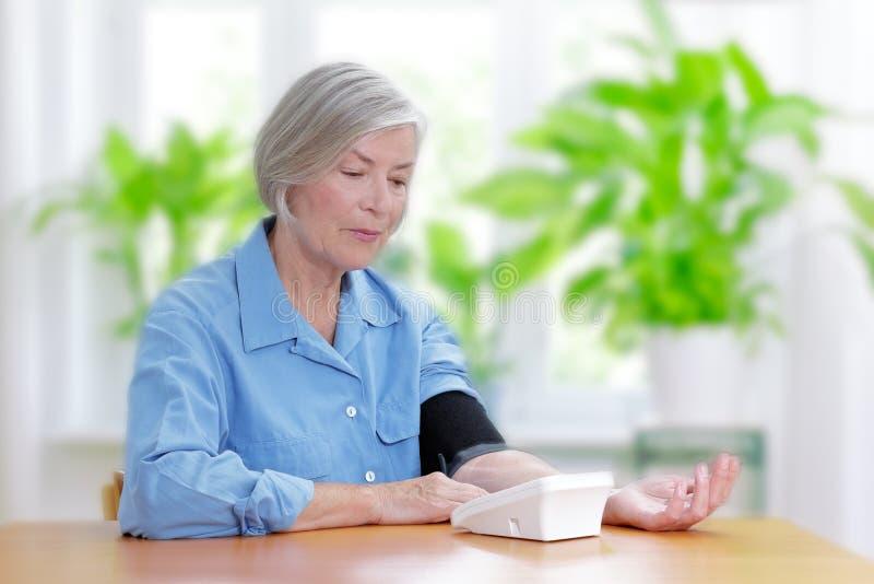 Pressione sanguigna di misurazione della donna senior fotografia stock