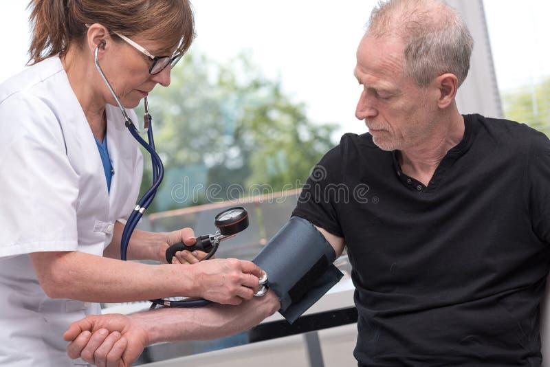 Pressione sanguigna di misurazione di medico con lo sfigmomanometro fotografie stock libere da diritti