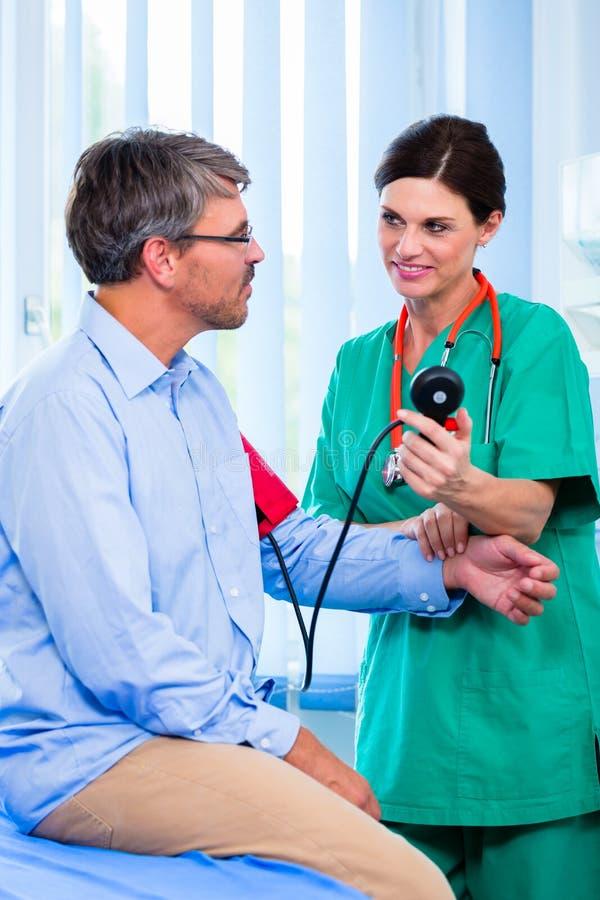 Pressione sanguigna di misurazione di medico sul paziente immagine stock libera da diritti