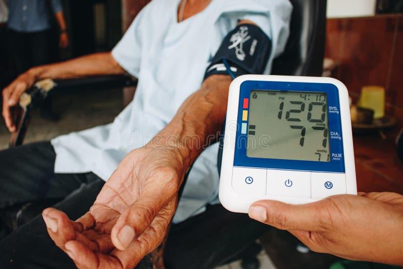 Pressione sanguigna di misurazione di medico dell'uomo anziano fotografie stock