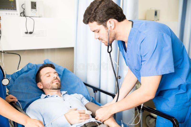 Pressione sanguigna di misurazione di medico di un paziente immagine stock libera da diritti