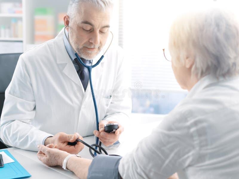 Pressione sanguigna di misurazione di medico di un paziente senior immagine stock libera da diritti