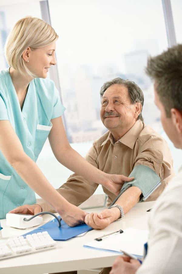 Pressione sanguigna di misurazione sorridente dell'infermiera del paziente fotografia stock libera da diritti